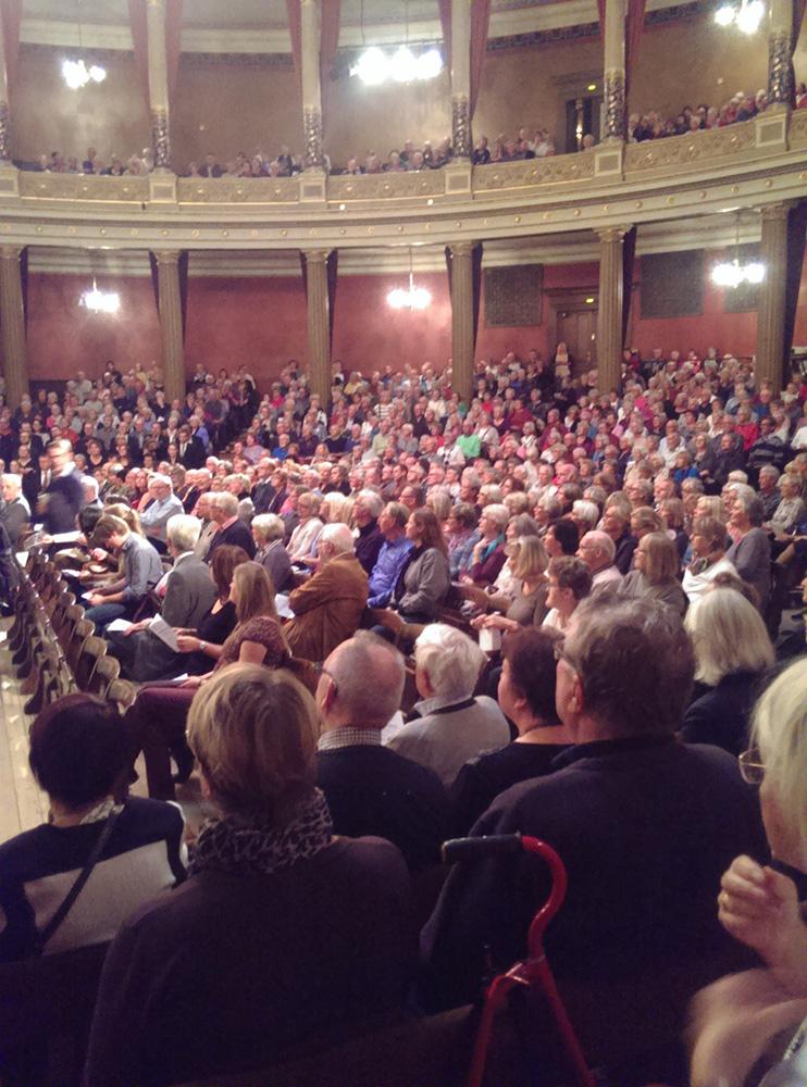 Fullt hus vid Uppsala universitets födelsedagsfirande i universitetsaulan.